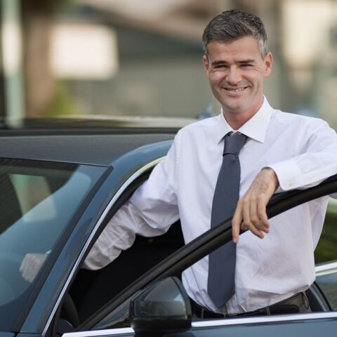 businessman-getting-in-his-car-picture-id623188282
